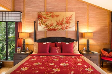 This over sized Asian inspired suite offers a Cal King bed and a calming view of the gardens. The en suite bathroom has a tiled sunken bath & shower. The sliding glass doors open onto a semi-private lanai deck, complete with chaise lounges.