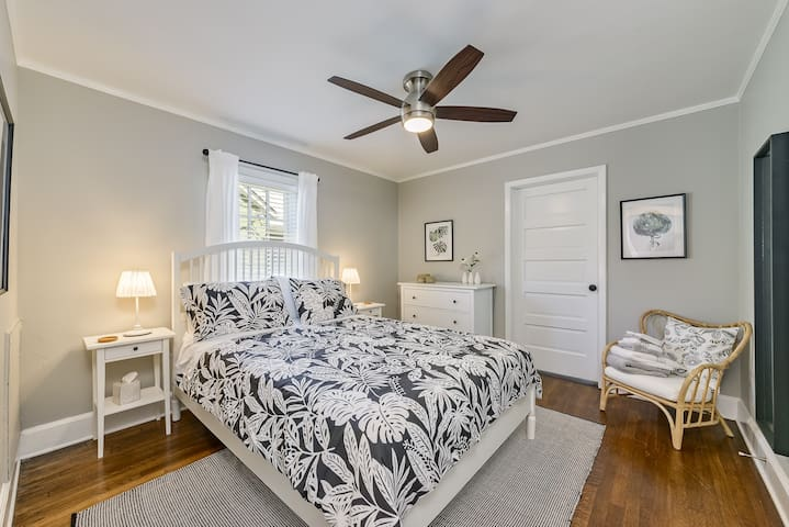 Beautiful master bedroom with comfortable queen bed, remote control ceiling fan, and door leading to delightful boudoir