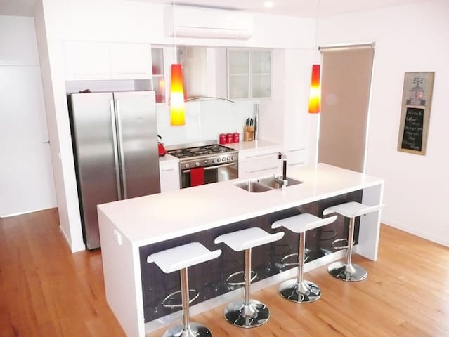 Contemporary and fully-equipped kitchen features stainless steel appliances and breakfast bar.