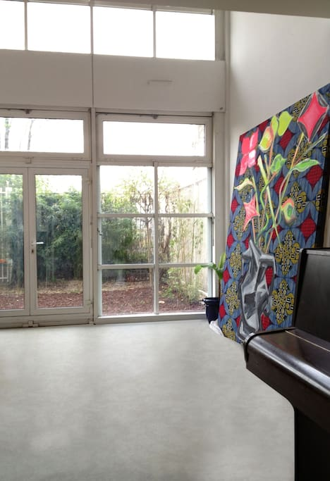 ground floor : artist's studio (35m2, large bay window and height ceiling) which opens directly on the private garden // rdc : grand atelier/salon en rez de jardin