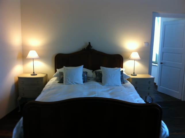 Large bedroom with traditional Limousin parquet flooring.  Views over the square.