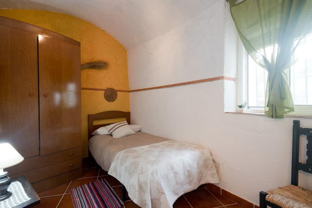Tercer Dormitorio de cueva Irene, ventana al exterior y confortable habitación individual.