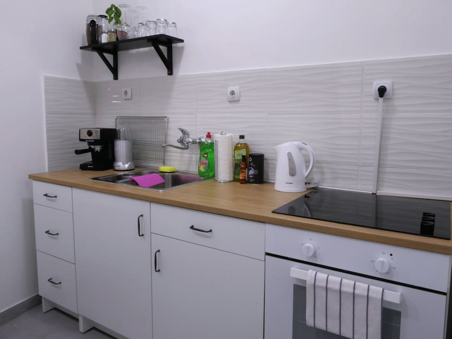 A fully equipped kitchen with top range coffee machine, stove, oven, water boiler, blender and of course pans, pots and all kinds of crockery, knives and cutlery