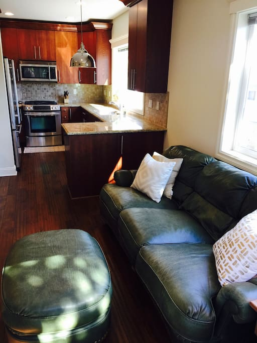 Full-sized leather sofa provides a comfortable place to sleep for an extra guest. Half-bathroom is located just off kitchen.