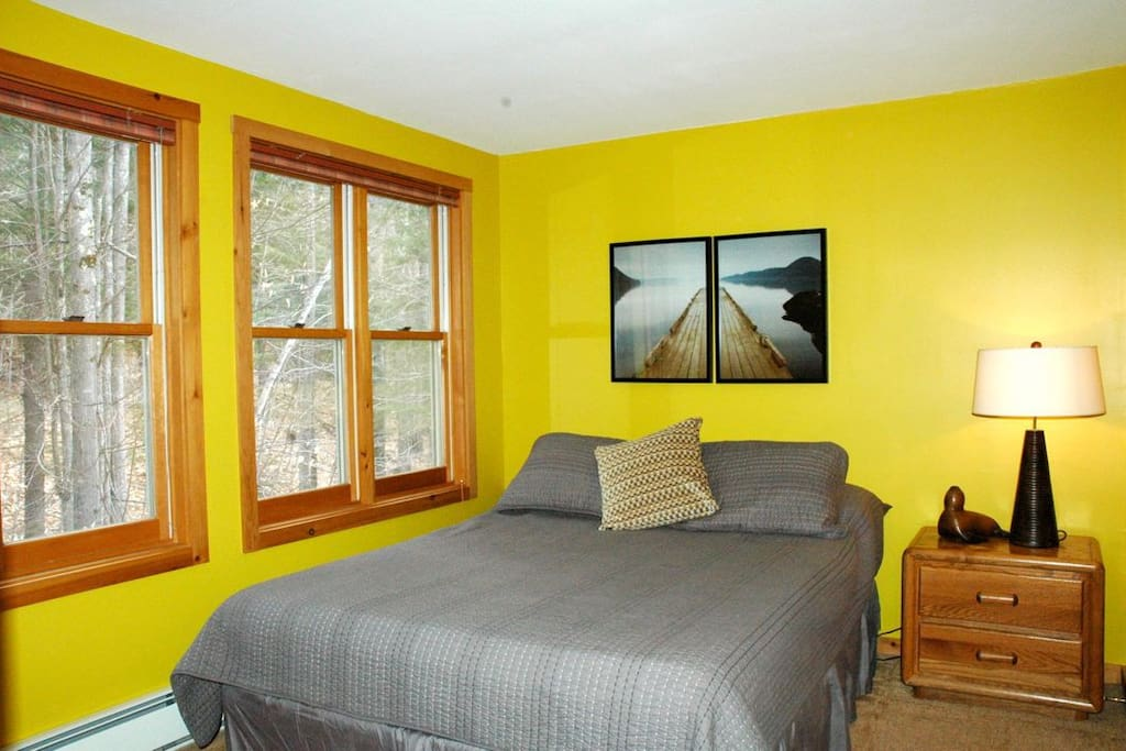 2nd bedroom with Queen bed and wooded view from wall of windows.