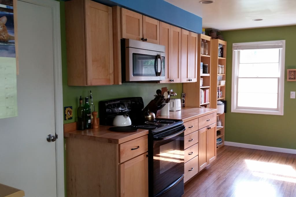 Sunny, renovated kitchen with custom cabinetry and bamboo flooring. All appliances: Stove, microwave, Asko dishwasher, refrigerator, and water filter.