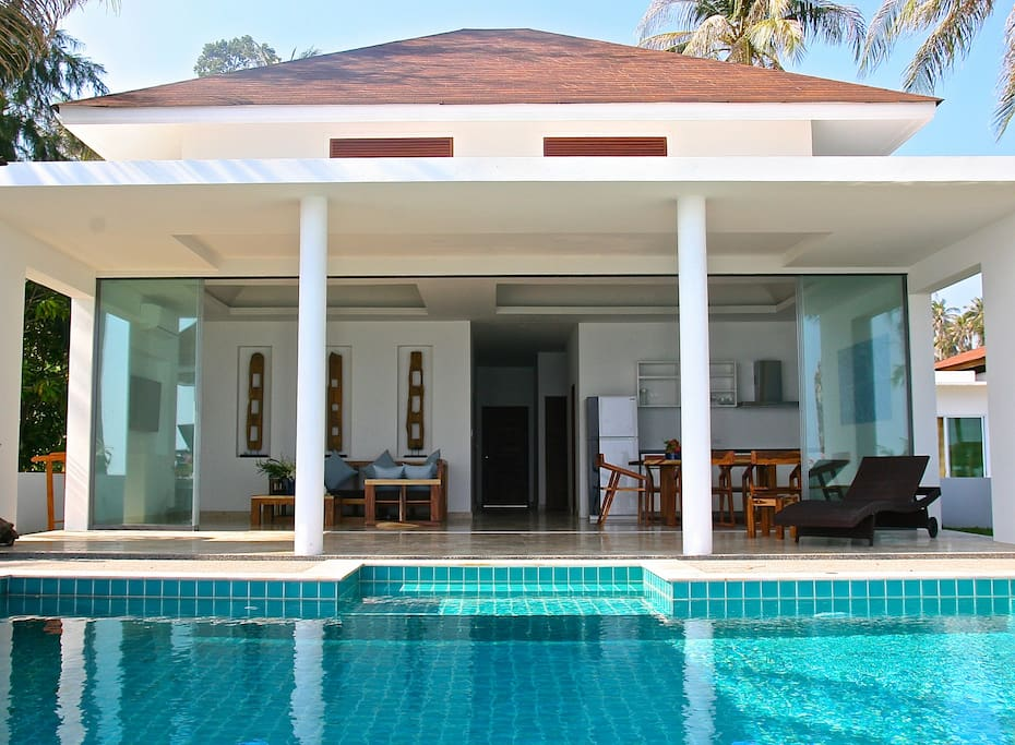 Front view of the villa - Roof to floor glass sliding doors that fold back to leave the entire kitchen and dining area open and looking directly out at your private swimming pool and the beach!