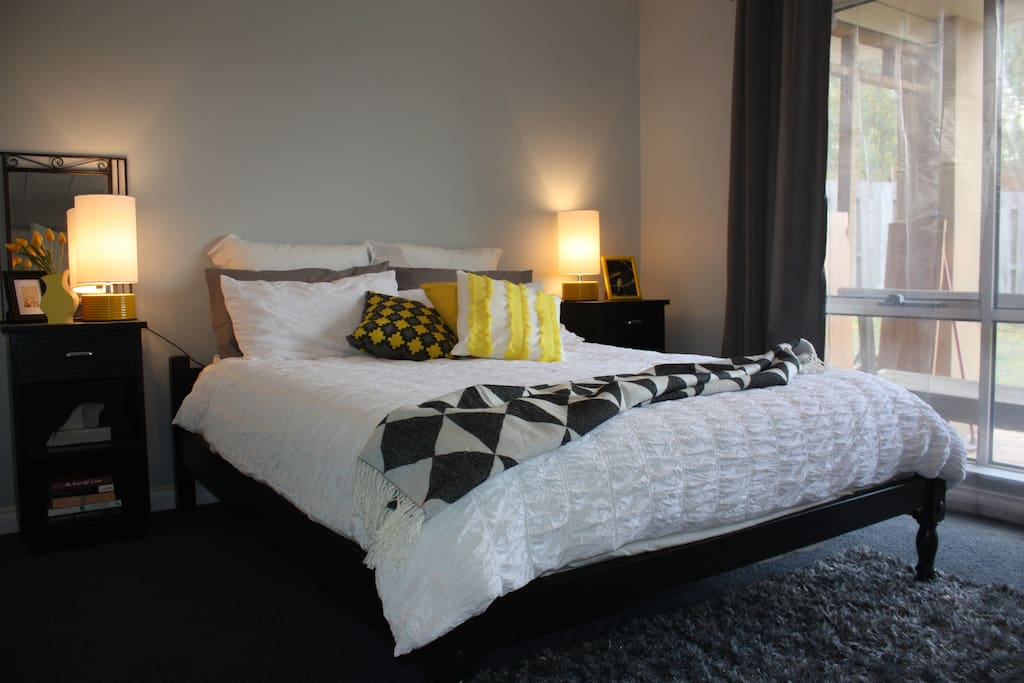 One of two large bedrooms. The yellow room has beautiful natural light, a queen size bed with electric blanket, bedside tables with lamps and storage.