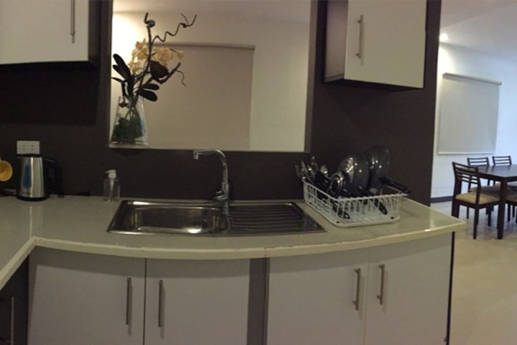 Full kitchen with pots and pans, cooking utensils, dining ware, chiller with freezer, living room with TV