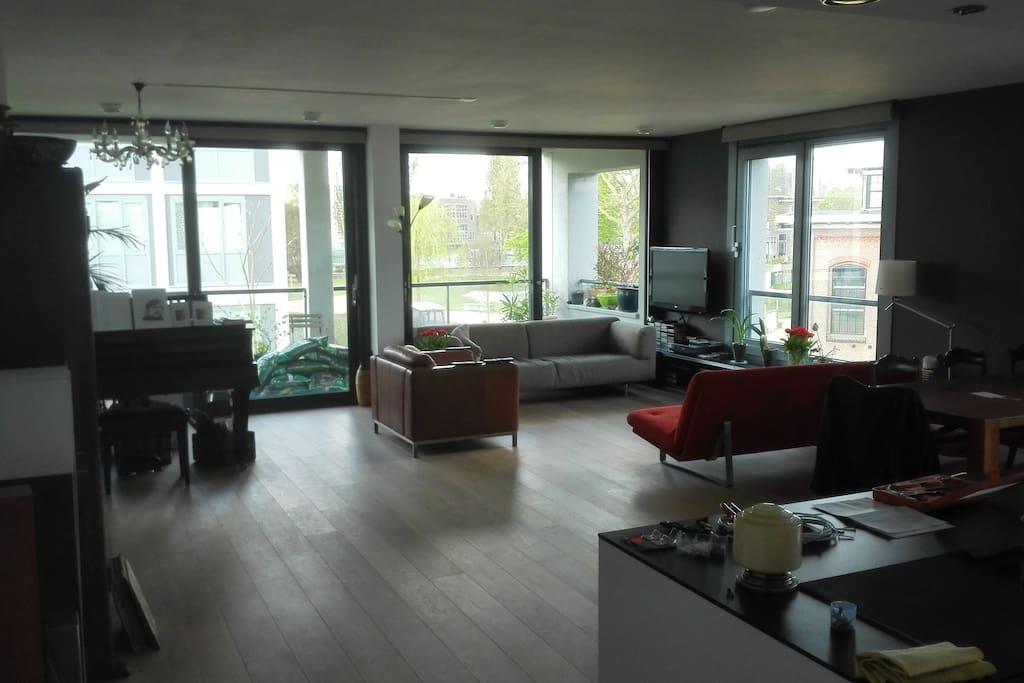 De grote woonkamer met uitzicht op het park en de singel