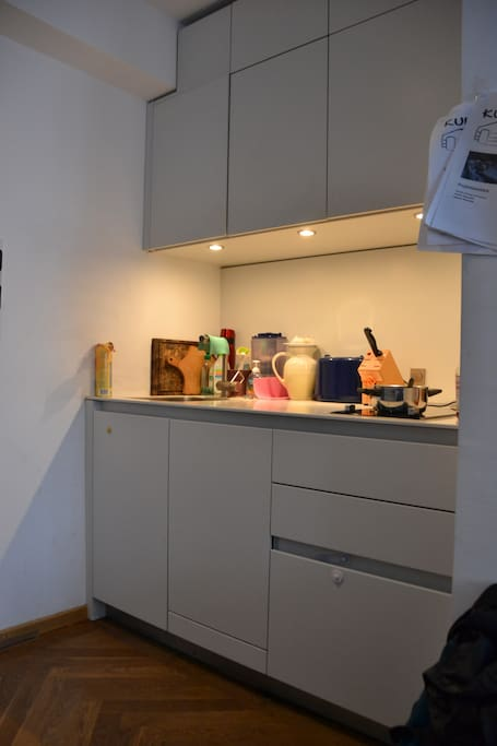 The kitchenette . Refrigerator and oven are in the back .