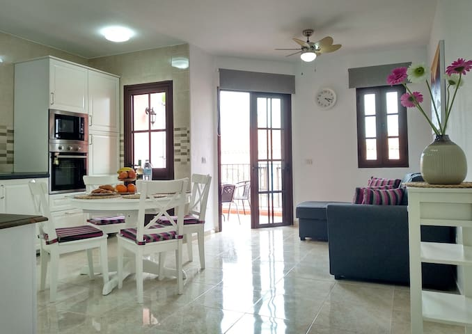 There are open area with a living room, dinning room and a kitchen. You can also see the entrance to the private terrace.