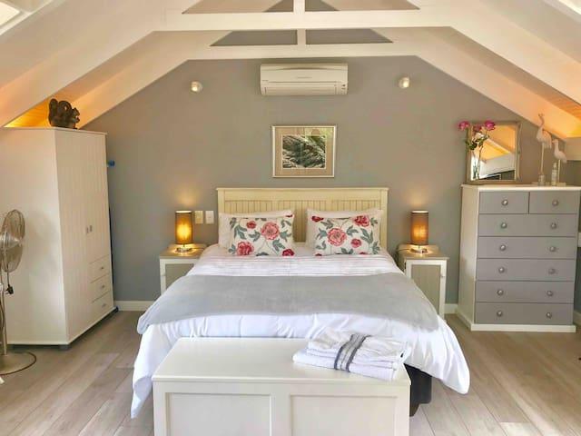 Romantic loft studio with white vaulted ceiling