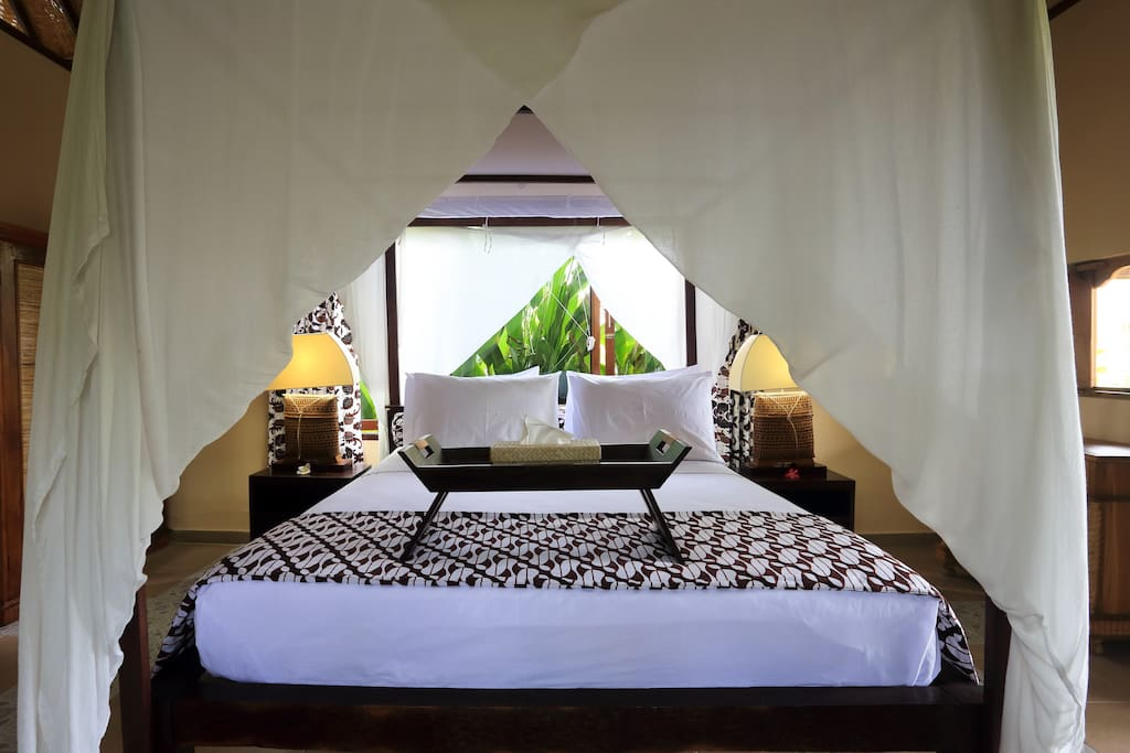 Large comfy bed with four posts and mosquito net