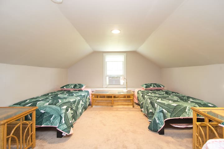 """The Flamingo """"Bunk Room"""" - upstairs room with multiple single beds and fun tropical/Flamingo-themed bedding. Perfect for kids and groups. Air mattress available for additional sleeping."""