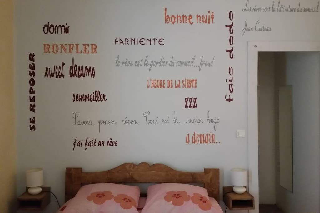 Phrases et mots autour du sommeil peintes sur le mur de la tête du lit.