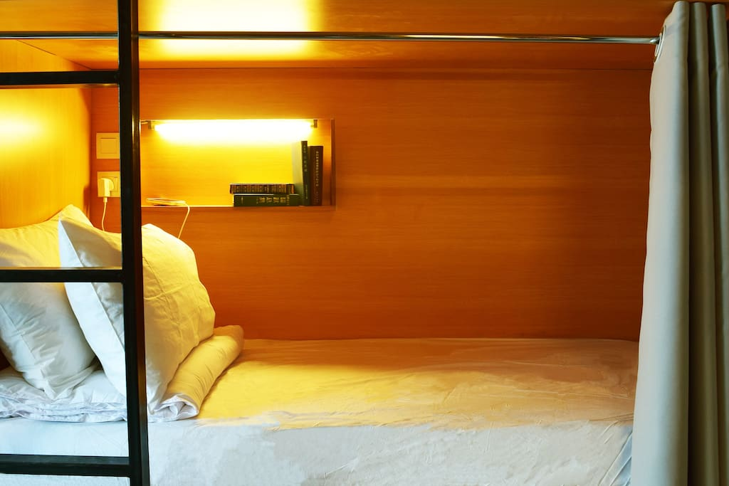 Comfy pod beds furnished with bed side lights, private curtains, lock-up cabinet, reading desk and power sockets