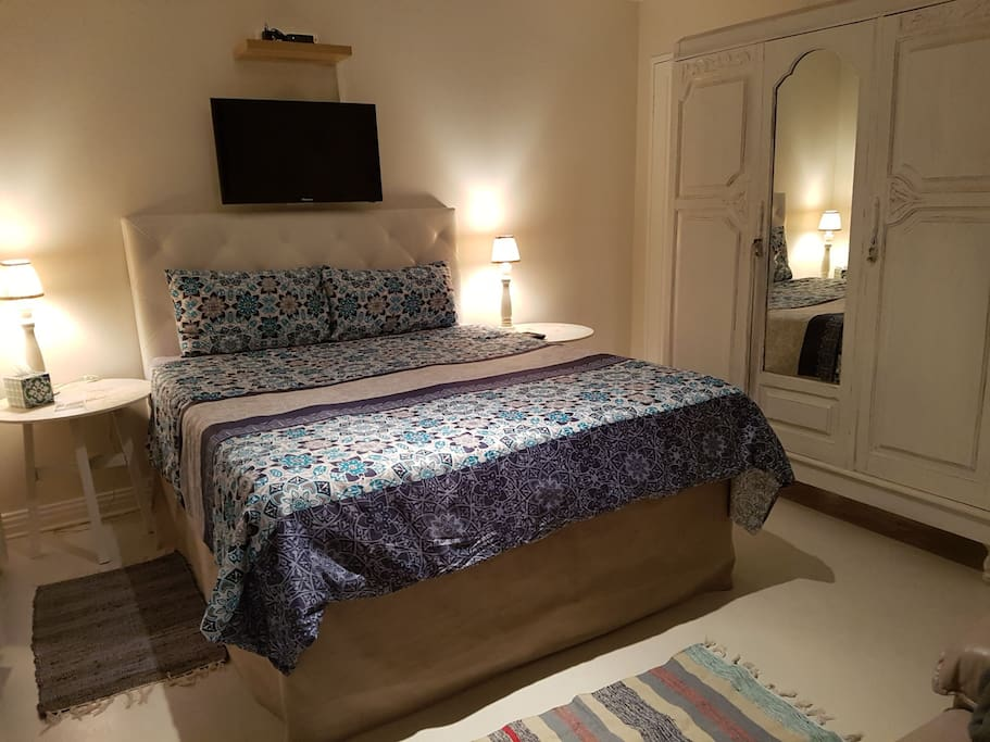 Bedroom consists of double bed with old fashioned wardrobe. The wardrobe serves as a divider  between the bathroom and bedroom.