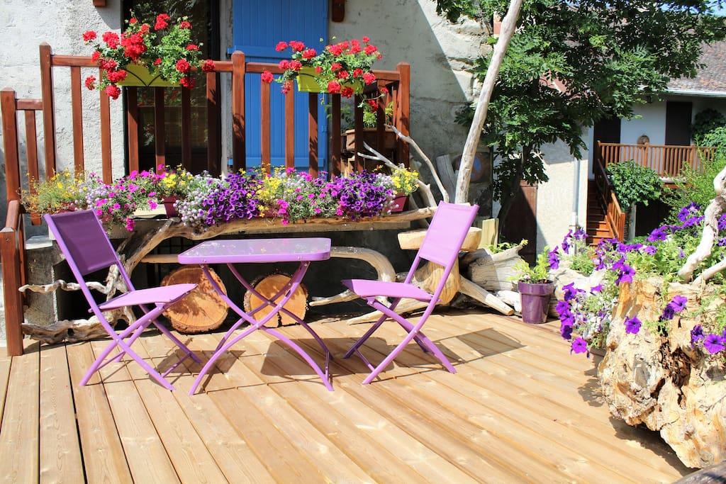 La terrasse du lodge en été, un petit coin de paradis au centre de Crots !
