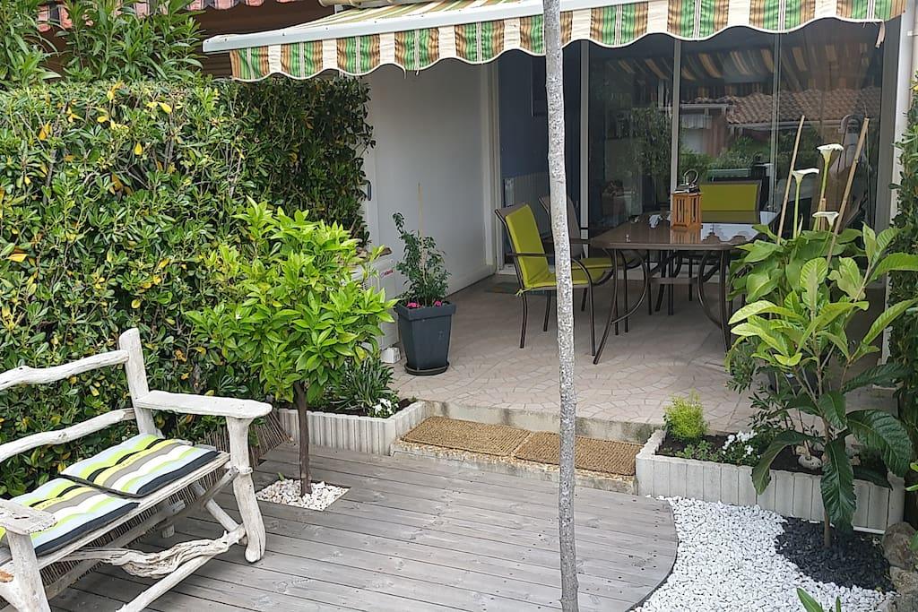 Salon de jardin dans un écrin de verdure.
