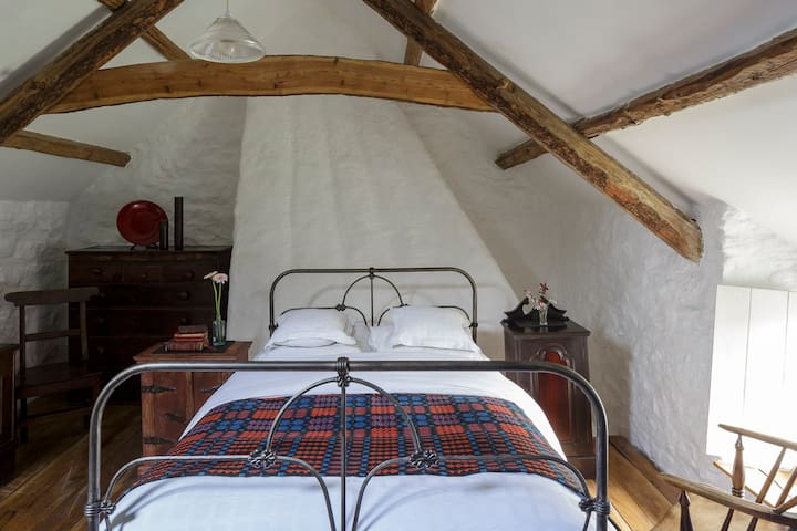 Master bedroom with exposed beams and traditional cast iron bed