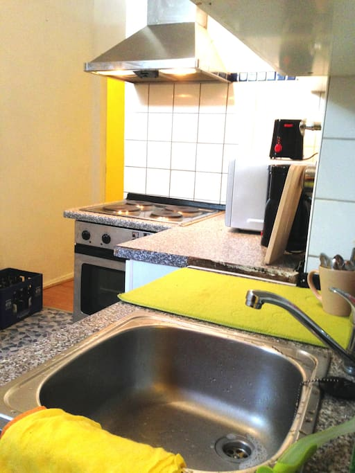 Gemeinschaftsküche mit Herd, Ofen, Mikrowelle, Kaffeemaschine, Wasserkocher, Toaster, Kühlschrank und Spüle.