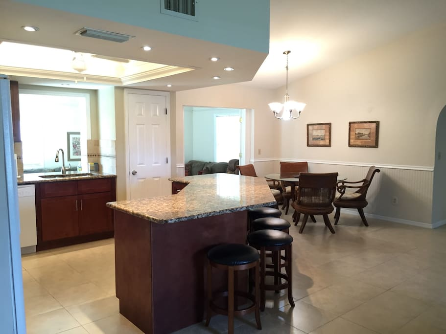 Large open concept livingroom with a custom granite and cherry kitchen and large breakfast island.