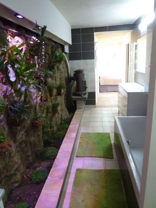 Suite parentale avec salle bain, baignoire, mur végétalisé, wc, chambre vue mer avec lit double en cuir