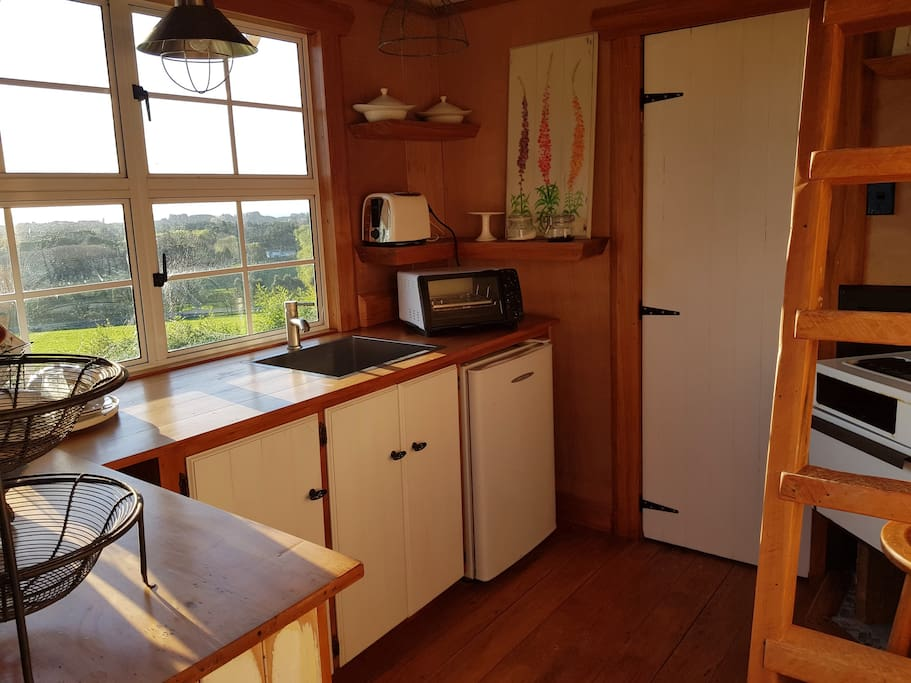 Lovely rimu kitchen with bathroom thru white door with shower and hand basin.....loft up the ladder and can sleep another adult....