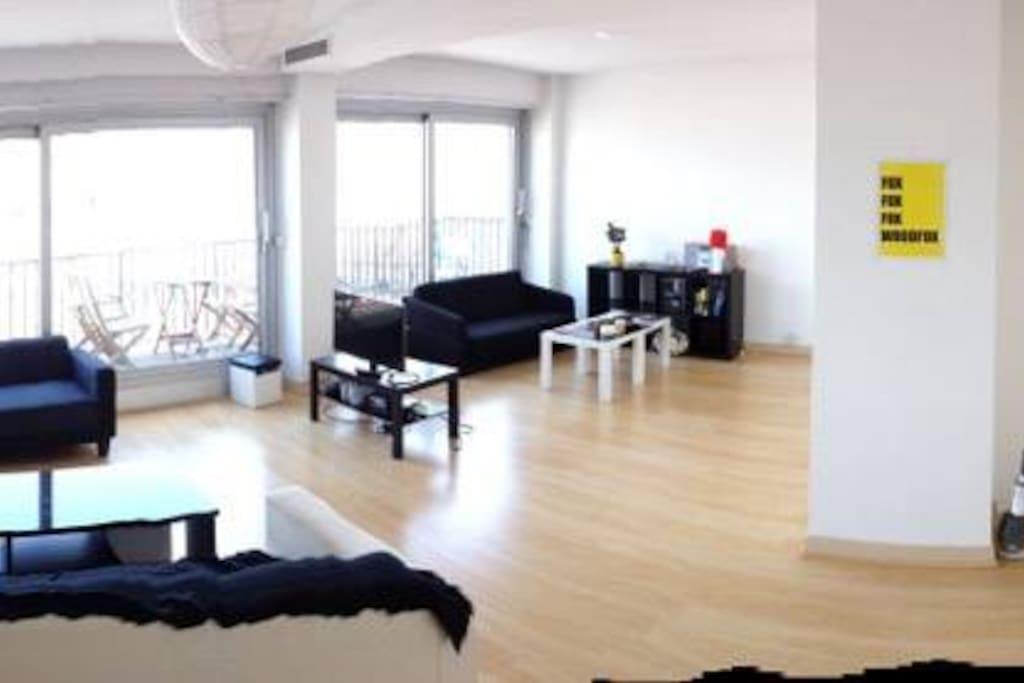 Salon avec plusieurs canapés et baies vitrées