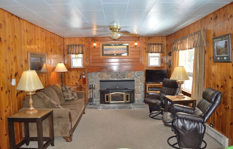 The spacious living room has a cozy wood burning fireplace.