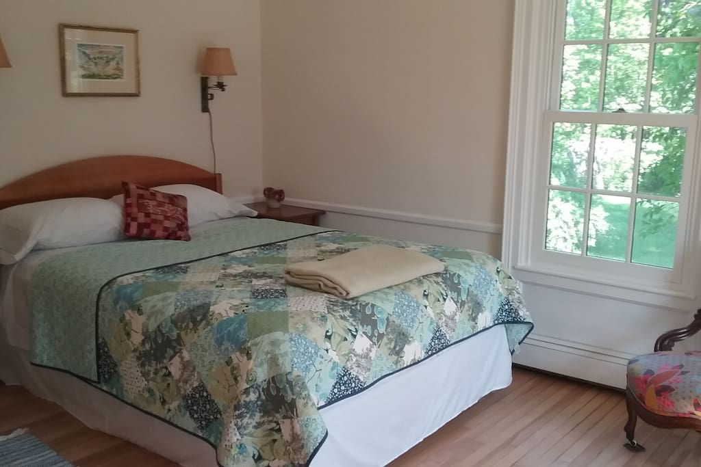 Queen bed in cheerful room with indirect morning sun.