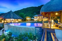 The cabana and infinity pool at night.