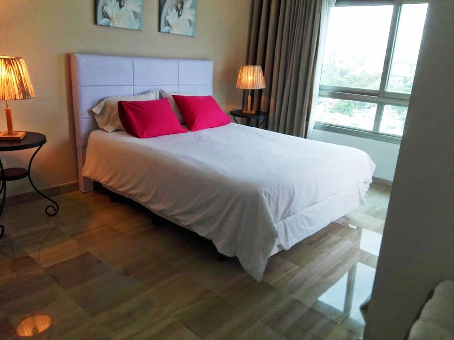 Well lit bedroom and very comfortable bed overlooking the city of Santo Domingo.