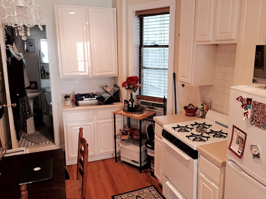 Classic Kitchen with fridge, stove and oven. Also includes a space with table and chairs for guests and eating