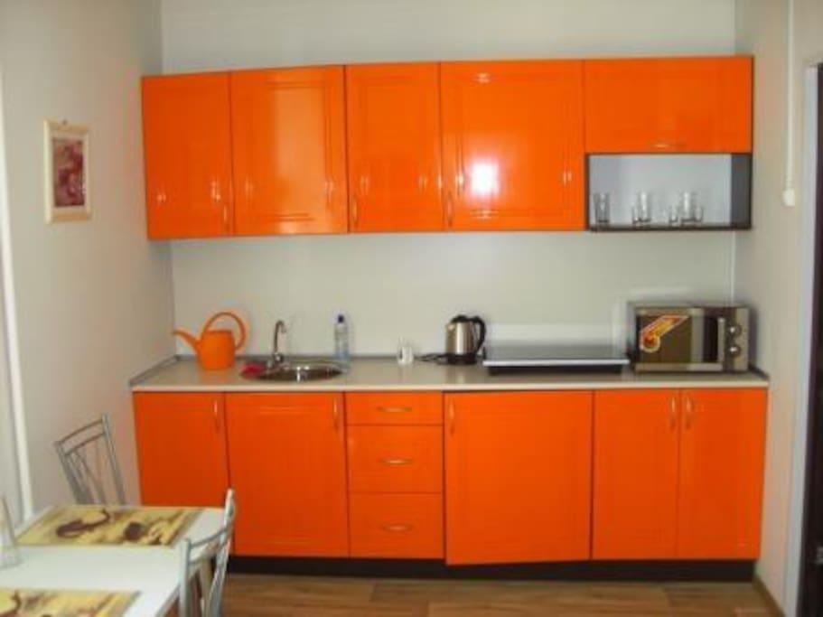 Просторная кухня, оснащенная оборудованием и посудой