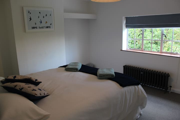 The upstairs master bedroom offers a king sized bed and looks out onto trees and birds