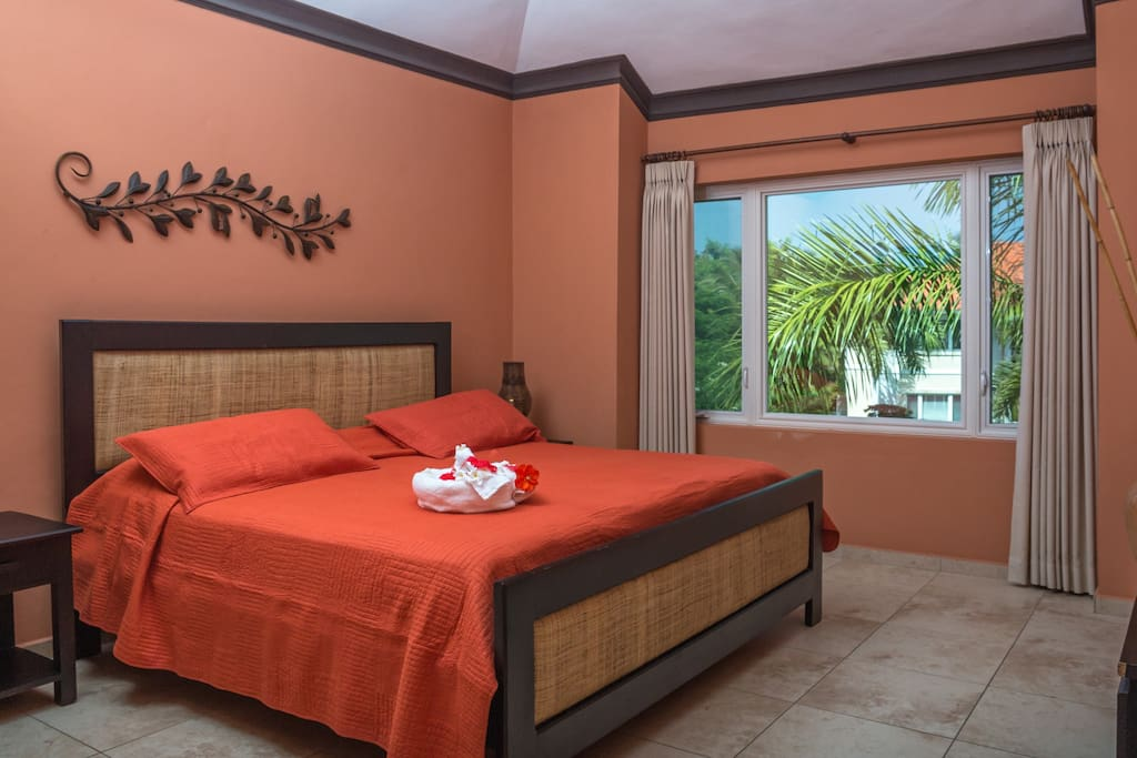 "The master charming bedroom's décor easily lures with its plush king size bed, en suite bathroom, spacious closet, 36"" plasma TV, and enticing view of the lush gardens and pool."
