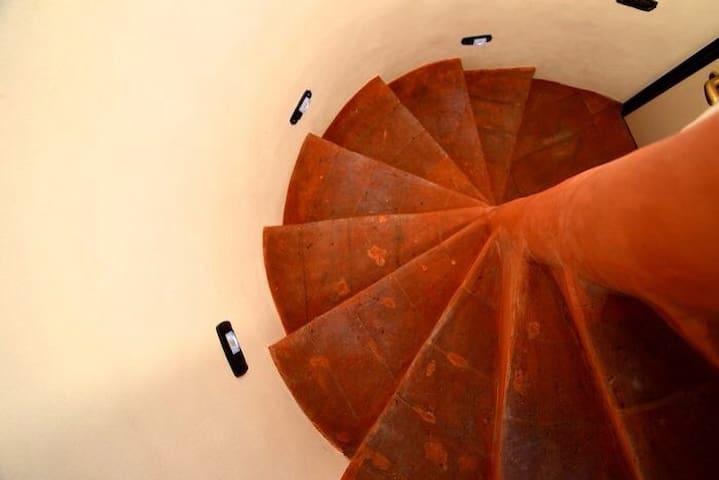 La scala a chiocciola in cotto del Seicento che conduce all'altana del B&B