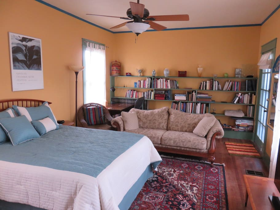 A beautiful room with queen bed, couch, desk, TV, fireplace, microwave, fridge and coffeepot.