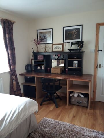 Workspace for laptop and comfortable chair to sit on. Kettle with tea and coffee. Hairdryer.