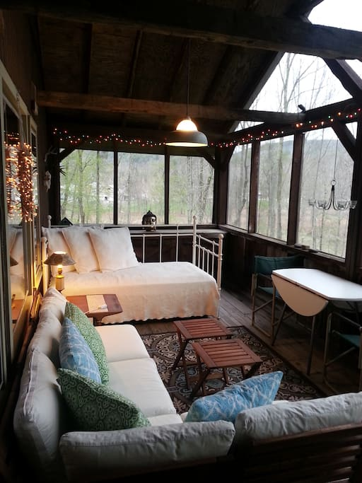 Screen porch with bed and trundle bed.