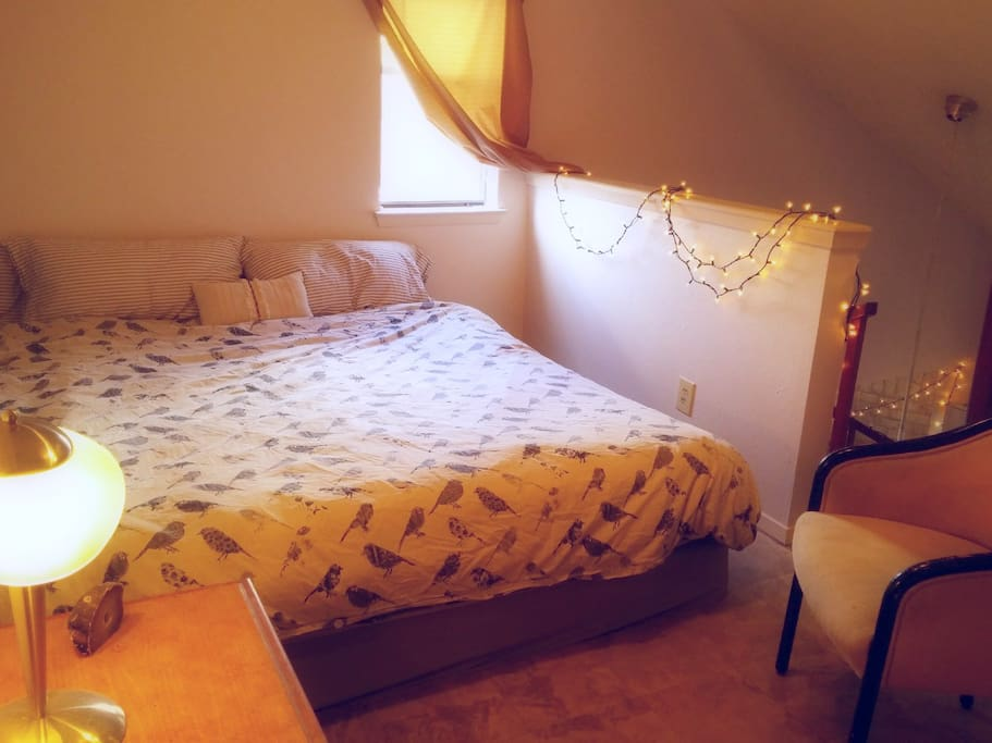 Cozy semi-private loft area with king bed, sitting area, and extra closet space.