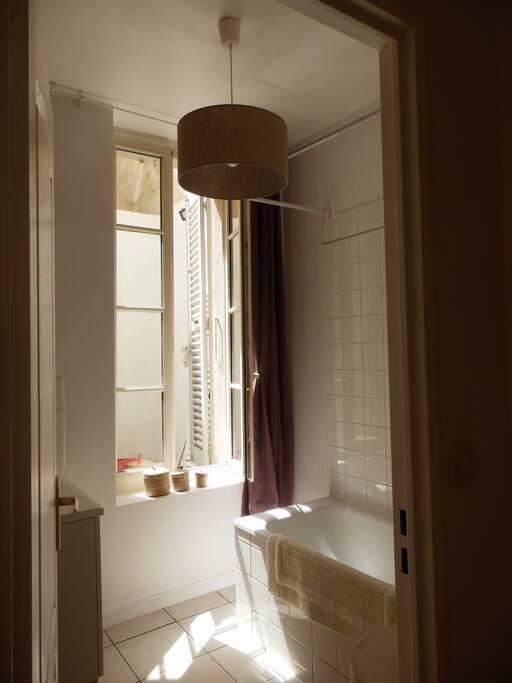 Salle de bain ensoleillée avec grande baignoire et fenêtre donnant sur la terrasse, sèche-serviettes et panier à linge