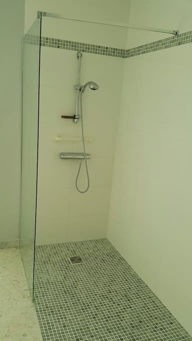 Douche à l'italienne avec mitigeur et poignets d'appui. Pare douche vitré.