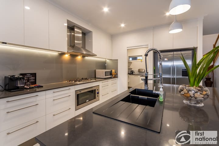 Kitchen with butlers pantry, fridge, freezer, gas cooktop, electric oven, stone bench tops