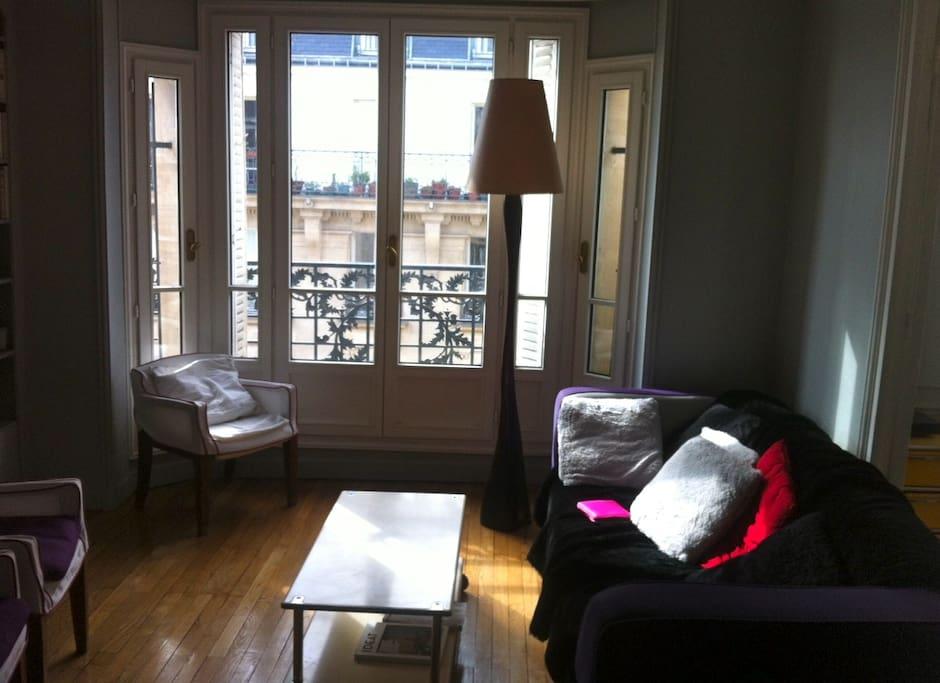 Double-salon lumineux, équipé d'un canapé, fauteuils, tv, chaine hifi, piano.
