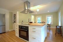 Kitchen with large center island, counter stools and dining area.