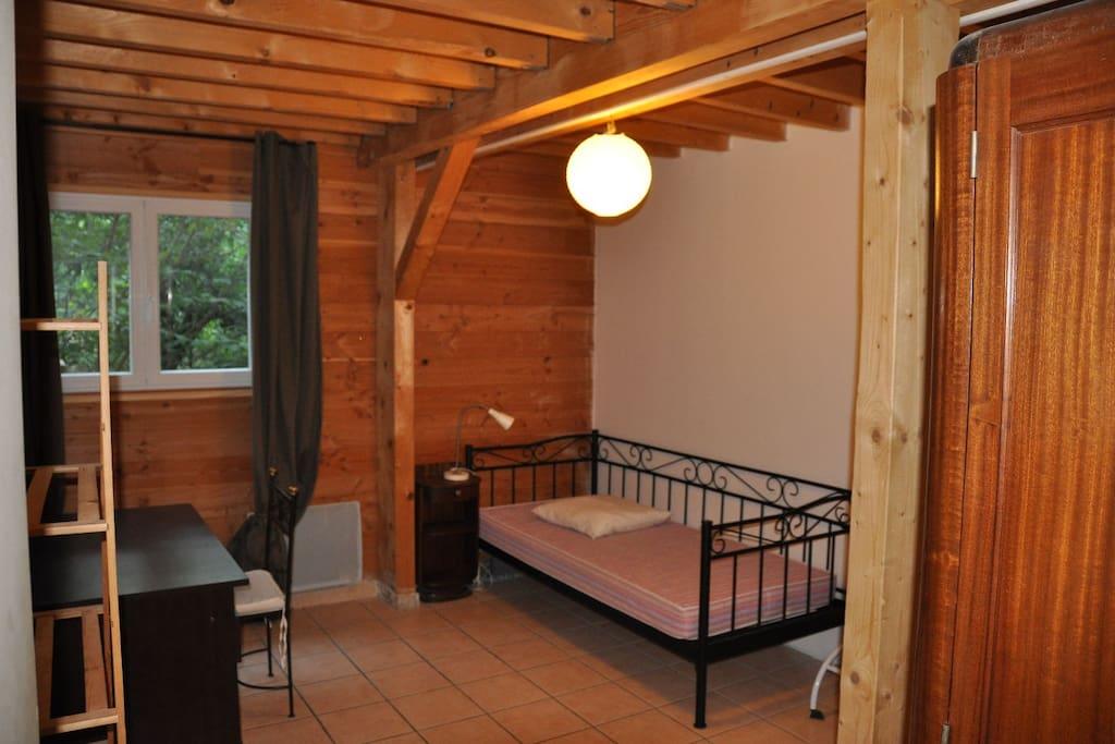 une chambre type avec un bureau et une armoire