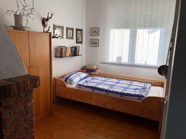 Einzelbett im Nachbarraum zum Wohnzimmer. Durch eine Schiebewand getrennt.